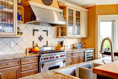 Yellow tones kitchen with tile decorated backsplash, kitchen appliances Stock Photo