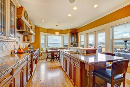 Yellow and white themes bright kitchen with hardwood floor, wood cabinets and  marble counter tops photo