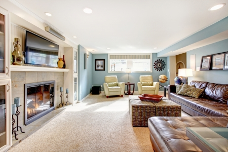 living room sofa: Light blue living room with leather furniture set, beige carpet floor, tv and fireplace