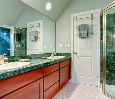 Light Green Bathroom With Vaulted Ceiling, Tile Floor And Brown Cabinets  Stock Photo   25561349