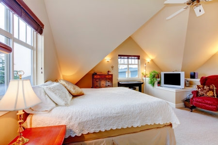 Beautifully designed light tones bedroom with bright brown cabinetes, beige carpet floor, cream color vaulted ceiling photo