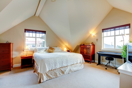 Vaulted ceiling  bright bedroom with wood furniture and piano photo