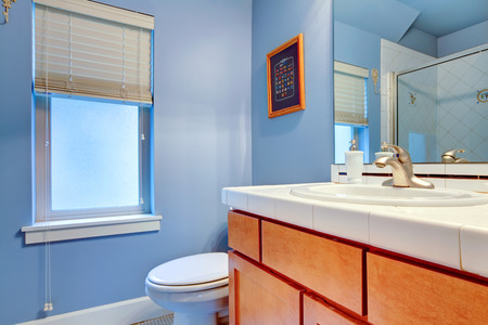 Light blue bathroom with brown wood cabinets and window Stock Photo - 25561367