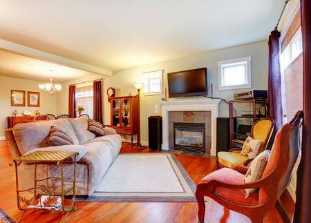 Furnished living room with fireplace and tv, open to rustic furnished dining area Stock Photo - 25561372