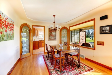 Ivory dining room with big window overlooking front porch. Furnished with rustic wood table set, decorated with old style pictures Stock Photo - 25561399