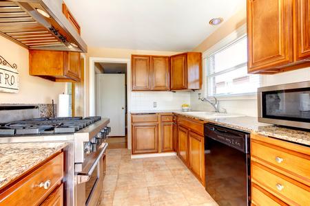 kitchen tile: Light tones kitchen room with wood cabinets, modern appliances, tile floor and tile backsplash