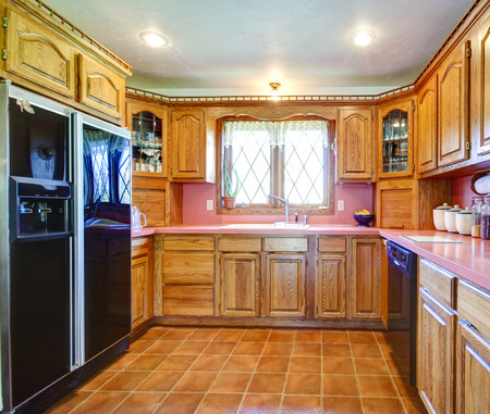 Tile floor kitchen room with black refrigerator, decorated wood cabinets photo