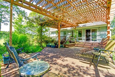 Grande idée pour ferme cour. Grande terrasse en bois étendu à pergola avec petit étang de jardin Banque d'images - 25561604