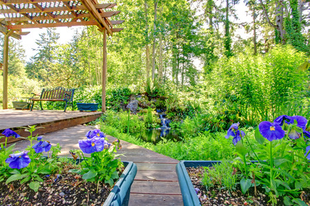 Farm house backyard deck view. Pond and waterfall, covered patio area with rustic old bench and flower pots Stock Photo
