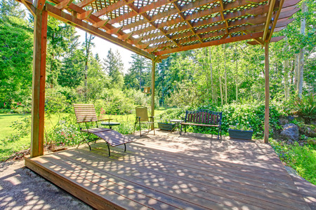 Open farm house pergola with rustic bench, chair and flower pots