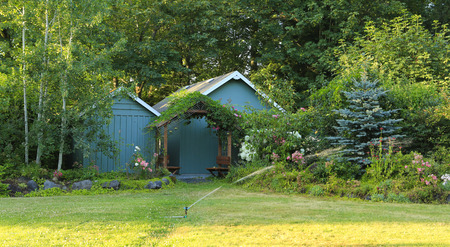 sheds: Farm house backyard with wood sheds, attached garden house,  flourishing flower bed Stock Photo