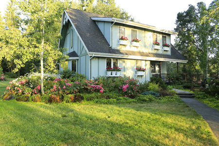 farm house: Mint color farm house with beautiful flourishing flower pots and amazing flowerbed