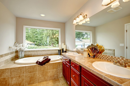 Bathroom with big window,  whirlpool, tile floor and bright cherry cabinets Stock Photo - 25561051