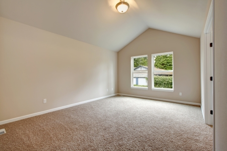 Soft colors empty room with valted ceiling, big window, carpet floor Stock Photo