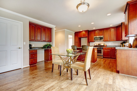 clean kitchen: Hardwood floor big kitchen room with cherry wood cabinets and light tones dining table set Stock Photo