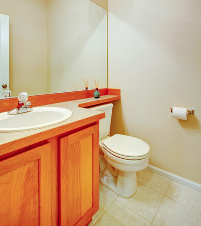 Small bathroom with wood cabinets and light tone tile floor Stock Photo - 25651318