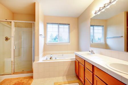 Elfenbein Badezimmer Mit Beige Fliesen Und Holz Schränke. Glastür Dusche  Und Whirlpool Erreichen Einander Standard