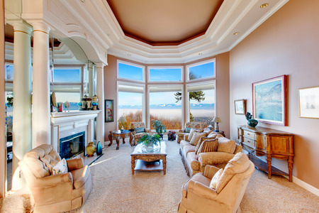 RIch furnished living room with coffered ceiling and colomns. Floor-to-ceiling angled window open a charming view on mountains Stock Photo - 25651367