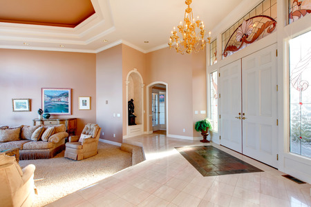 Open plan of luxury hallway and living room. White entrance door well matched with  beige concrete floor and walls