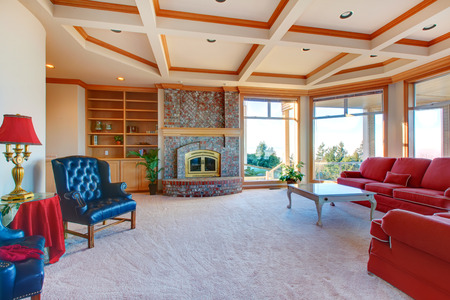 Bright family room with brick background fireplace, coffered ceiling, red couch and chair photo