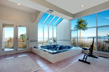 White glass wall room for exercising with whirlpool. Big glass wall opens a wonderfull landscape view Фото со стока