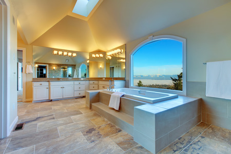 Large luxury bathroom with concrete floor, cathedral ceiling, whirlpool and arch window overlooking amazing mountain landscape photo