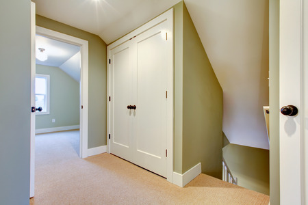 residential houses: White and olive hallway with beige carpet floor, vaulted ceiling and bulit-in storage room Stock Photo