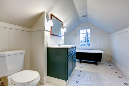 White bathroom with vaulted ceiling. Antique style bath tub, green wood cabinet accomplish old-style theme photo