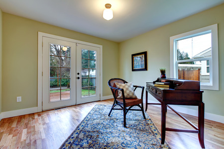 furnished: Bright living room with walkout deck furnished with antique desk and rustic chair. Stock Photo