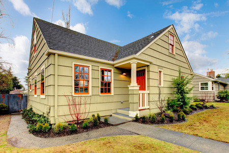 curb appeal: Olive house with red front door and orange window treatment.