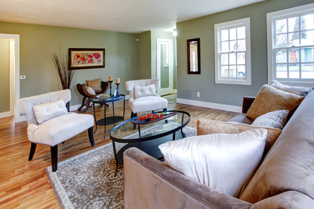classic living room: Aqua living room with brown rug, sofa and white classic chairs. Antique chair with pillows and dry branches accomplish  old style atmosphere