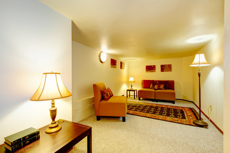 Bright room with orange furniture, rug and lamps.  Decorated with wall picrures and printed pillows