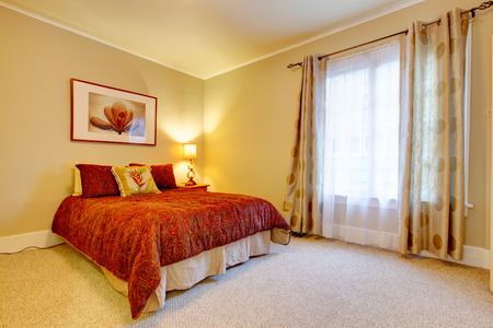 window treatments: Bright bedroom with beige carpet floor and yellow walls. Red bedding and red frame wall picture accomplish  design
