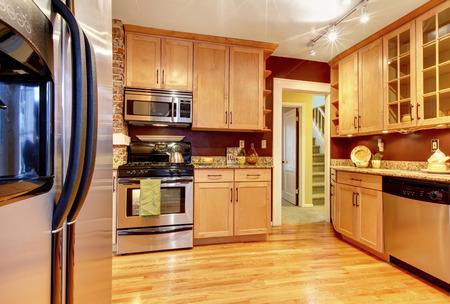 Impressive kitchen with burgundy backsplash, brick wall, wood storage combination and hardwood floor photo