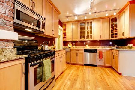 Impressive kitchen with burgundy backsplash, brick wall, wood storage combination and hardwood floor