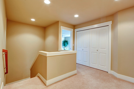 upstairs: Upstair hallway with beige carpet floor and stairs. Stock Photo
