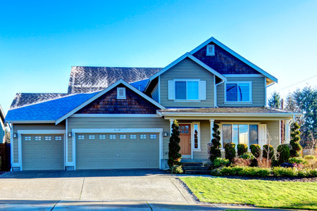 cladding tile: Pretty siding house with colomn porch  and attached garage. The green lawn with flower bed and trimmed hedges Stock Photo