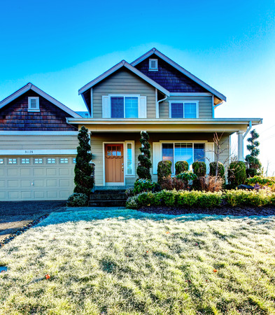 Pretty siding house with colomn porch  and attached garage. The green lawn with flower bed and trimmed hedges Stock Photo