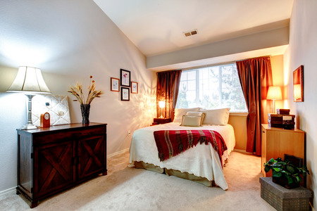 Cozy bedroom with high vaulted ceiling furnished with antique cabinet and queen size bed Stock Photo - 25668335
