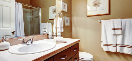 bathroom wall: Warm colors bathroom decorated with white towes and wall picture Stock Photo