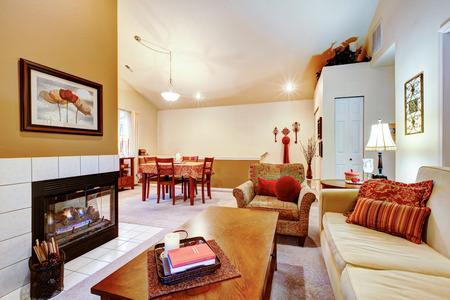 아이보리 dinig 지역 및 체리 식탁 세트와 잘 어울리는 벽난로가있는 따뜻한 색 거실 스톡 콘텐츠