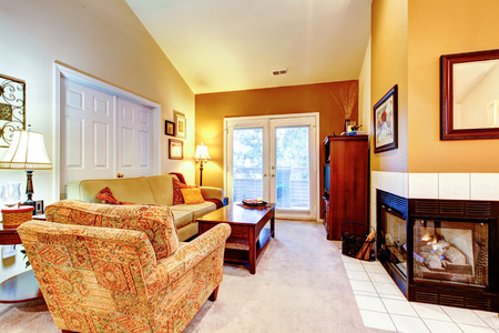 Small cozy living room with fireplace, wood coffee table and cabinet, mustard sofa and chairs. photo