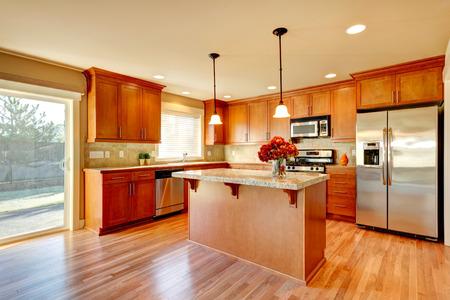 on wood floor: Bright kitchen with hardwood floor, wood cabinets, modern steel appliances and tile back splash Stock Photo