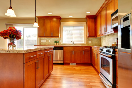 Bright kitchen with hardwood floor, wood cabinets, modern steel appliances and tile back splash photo