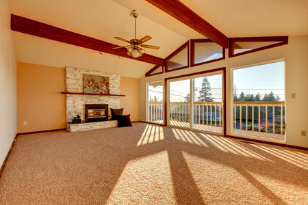 Living room with vaulted ceiling and beams, stoned background fireplace, beige carpet floor and walkout deck Stock Photo