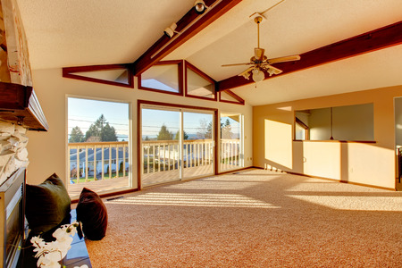 vaulted: Living room with vaulted ceiling and beams, stoned background fireplace, beige carpet floor and walkout deck Stock Photo