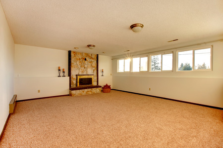 carpet: Bedroom with stoned background fireplace and beige carpet floor