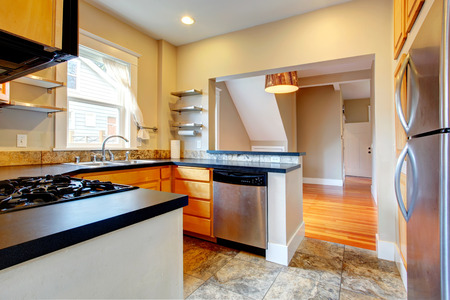 Modern kitchen with wood storage, black counter tops, steel appliances  and concrete floor photo
