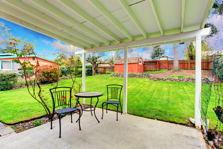 pergola: Attached pergola with patio table set overlooking beautiful green lawn, trees and red wooden shed