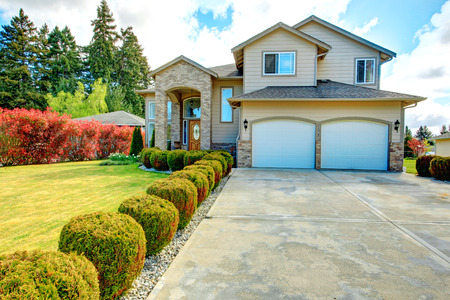 driveways: Big siding house with garage and high column porch. Green lawn with trimmed hedges and red bushes make the curb appeal stand out